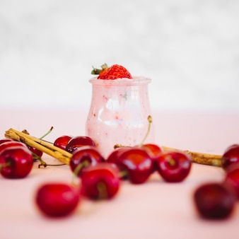 Nahaufnahme von roten kirschen mit erdbeeresmoothie auf rosa schreibtisch