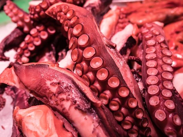 Nahaufnahme von roten oktopus-tentakeln im meeresfrüchtemarkt.