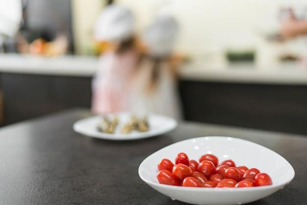 Nahaufnahme von roten tomaten in der weißen schüssel über küchenarbeitsplatte