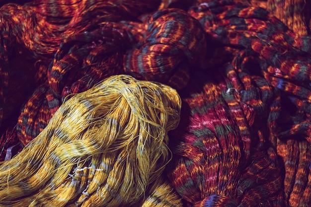 Nahaufnahme von roter und gelber farbe binden seidengarn zum weben, thai mudmee stoff, seidengarn aus natürlichen materialien gefärbt