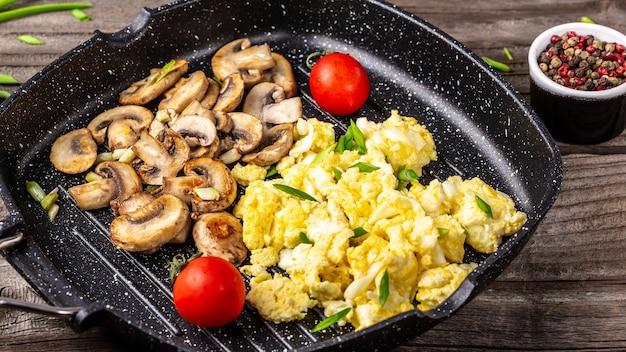 Nahaufnahme von rührei mit champignonpilzen in der pfanne.