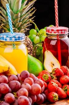 Nahaufnahme von saftigen früchten und von saftglas gegen schwarzen hintergrund