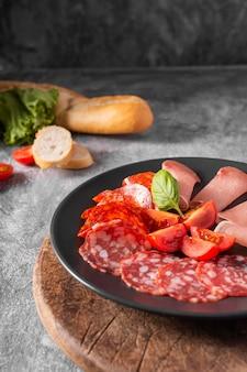 Nahaufnahme von salami und tomaten auf teller