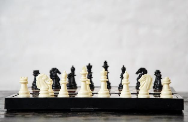 Nahaufnahme von schachfiguren, die zu beginn des spiels auf das schachbrett gelegt wurden