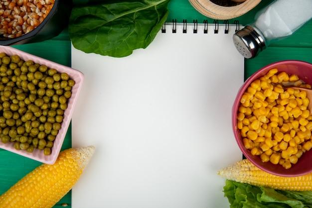 Nahaufnahme von schalen mit maissamen und grünen erbsen mit corns-spinatsalz und notizblock auf grünem hintergrund mit kopienraum