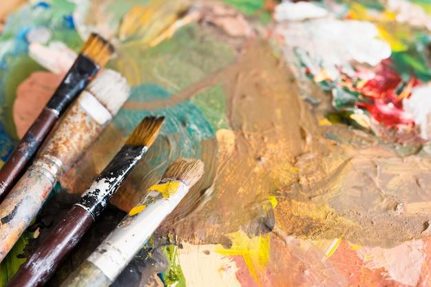 Nahaufnahme von schmutzigen malerpinseln über öl gemalter oberfläche