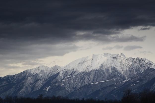 Nahaufnahme von schneebedeckten bergen in den alpen mit dunklen wolken