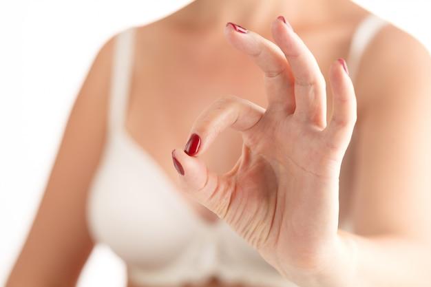 Nahaufnahme von schöne weibliche hände mit roten nägeln auf weißer oberfläche