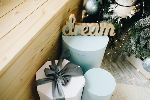 Nahaufnahme von schönen verpackten weihnachtsgeschenken neben geschmücktem weihnachtsbaum