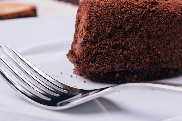 Nahaufnahme von schokoladenkuchen und gabel im vordergrund
