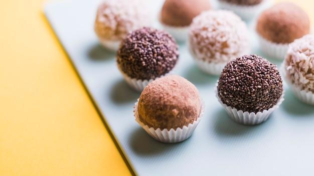 Nahaufnahme von schokoladentrüffeln auf weißem behälter gegen gelben hintergrund