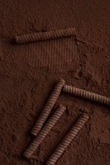 Nahaufnahme von schokoladenwaffelrollen, die mit pulver bedeckt sind
