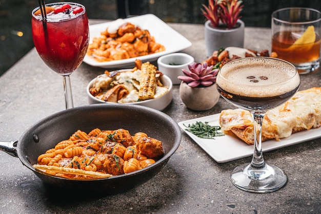 Nahaufnahme von schüsseln mit gekochten nudeln mit salaten, köstlichen cocktails und gebratenem gemüse auf dem tisch