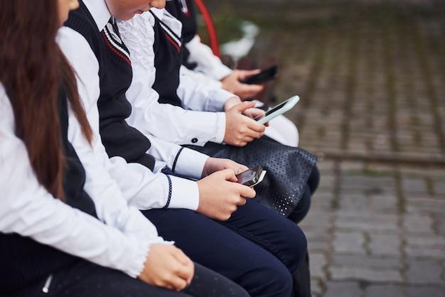 Nahaufnahme von schulkindern in uniform, die mit smartphones auf der bank sitzt.