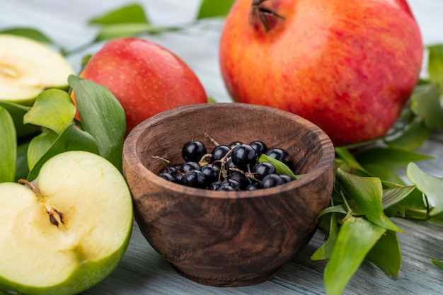 Nahaufnahme von schwarzdornbeeren in der schüssel mit ganzem und halb geschnittenem apfel mit granatapfel und blättern