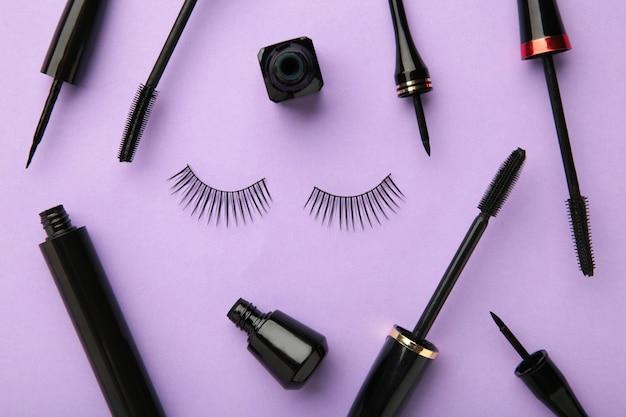 Nahaufnahme von schwarzen eyelinern und mascara-pinsel auf lila hintergrund. ansicht von oben.
