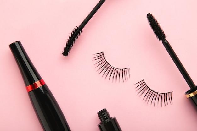 Nahaufnahme von schwarzen eyelinern und mascara-pinsel auf rosa hintergrund. ansicht von oben.
