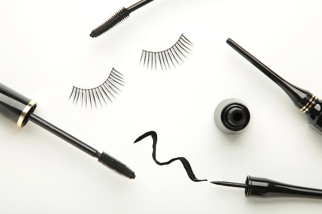 Nahaufnahme von schwarzen eyelinern und mascara-pinsel auf weißem hintergrund. ansicht von oben.
