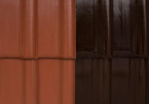 Nahaufnahme von schwarzen und roten keramikfliesen auf dem dach