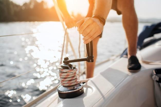 Nahaufnahme von seemann windet sich um seil, indem griff zum aufwickeln verwendet wird. er arbeitet mit beiden händen. junger mann steht auf yacht.
