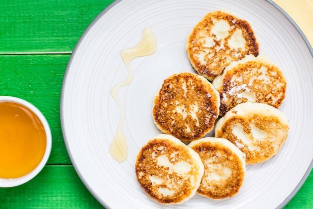 Nahaufnahme von selbst gemachten hüttenkäsepfannkuchen mit honig auf einer platte auf einem holztisch. ansicht von oben