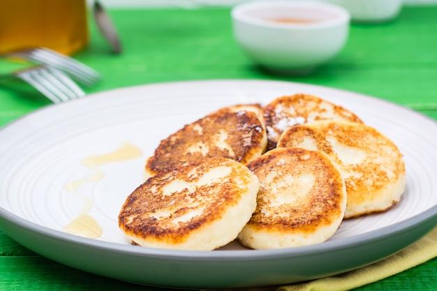 Nahaufnahme von selbst gemachten hüttenkäsepfannkuchen mit honig auf einer platte auf einem holztisch