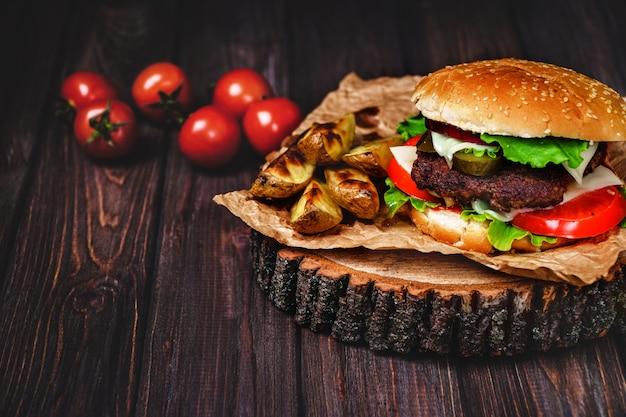 Nahaufnahme von selbst gemachten rindfleischburgern mit kopfsalat und majonäse diente auf wenigem hölzernem schneidebrett.