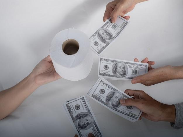 Nahaufnahme von sellbuy-tissue-hand hält toilettenpapier und geld von 100 us-dollar-banknote