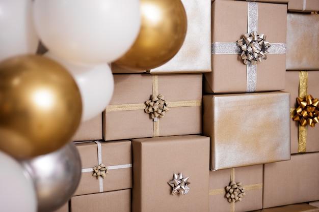 Nahaufnahme von silbernen und goldenen ballons mit weihnachtsgeschenken