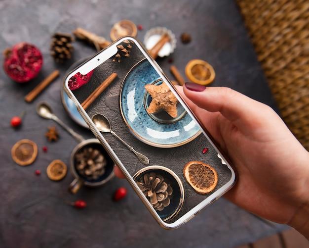 Nahaufnahme von smartphone hielt auf plätzchen mit getrockneten zitrusfrucht- und kiefernkegeln