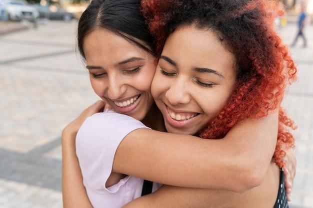 Nahaufnahme von smiley-frauen, die sich umarmen