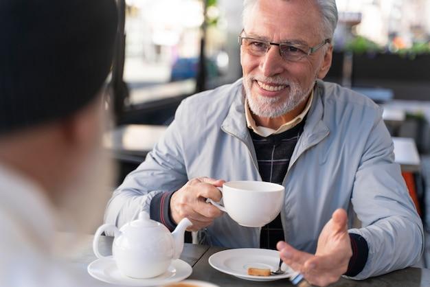 Nahaufnahme von smiley-freunden, die am tisch sitzen