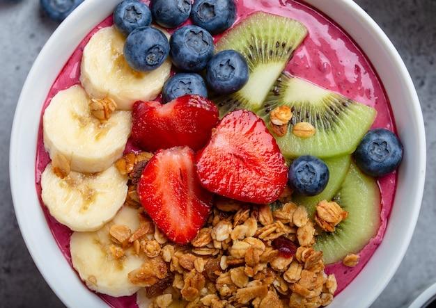 Nahaufnahme von sommer-acai-smoothie-schalen mit erdbeeren, banane, blaubeeren, kiwi und müsli auf grauem betonhintergrund. frühstücksschüssel mit obst und müsli, draufsicht, gesundes essen