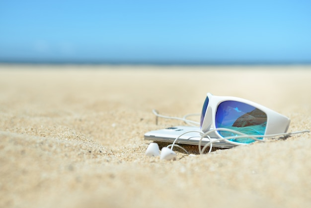 Nahaufnahme von sonnenbrille und telefon am strand