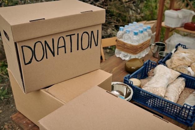 Nahaufnahme von spendenboxen, die auf holztisch mit lebensmittelvorräten für flüchtlinge im freien stapeln