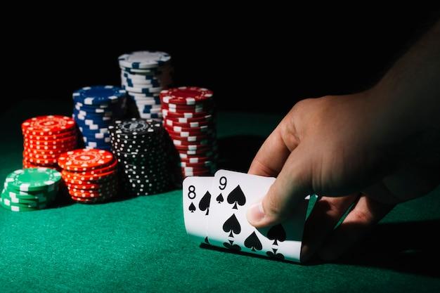 Nahaufnahme von spielkarten einer person auf kasinotabelle