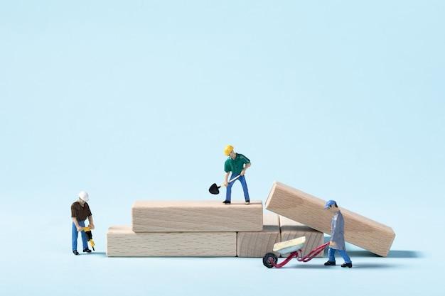 Nahaufnahme von spielzeugbauarbeitern, die ihren job auf einer blauen wand tun