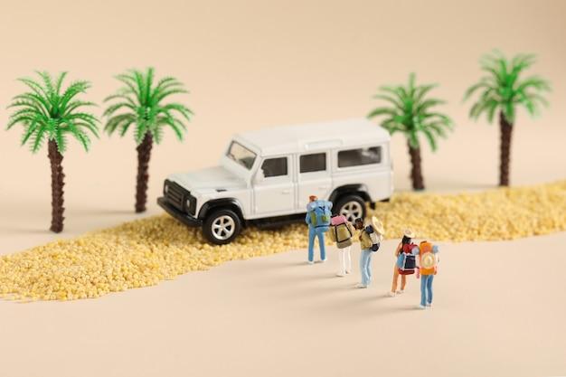 Nahaufnahme von spielzeugfiguren einer reisenden familie in der nähe eines autos