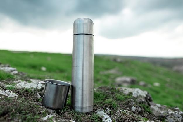 Nahaufnahme von stahl-edelstahl-thermoskanne und tasse auf stein im grünen feld.