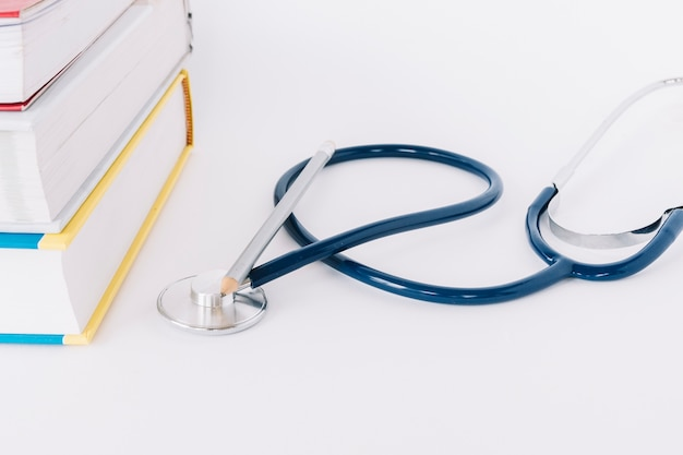 Nahaufnahme von staplungsbüchern und von stethoskop auf weißem hintergrund