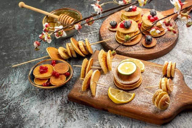 Nahaufnahme von stickigen pfannkuchen auf schneidebrett und honig auf der linken seite des grauen tisches