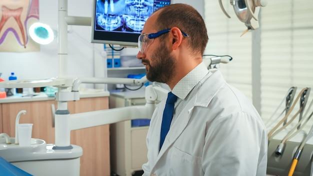 Nahaufnahme von stomatologen im gespräch mit frau in zahnklinik. arzt und krankenschwester arbeiten in einem modernen stomatologischen büro zusammen und erklären die röntgenaufnahme der zähne vom digitalen monitor im hintergrund