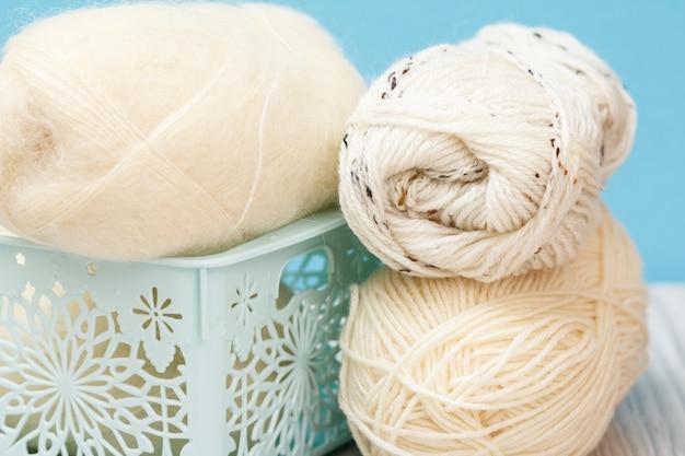 Nahaufnahme von strickgarnkugeln im plastikkorb mit blauem hintergrund. strickkonzept. geringe schärfentiefe.