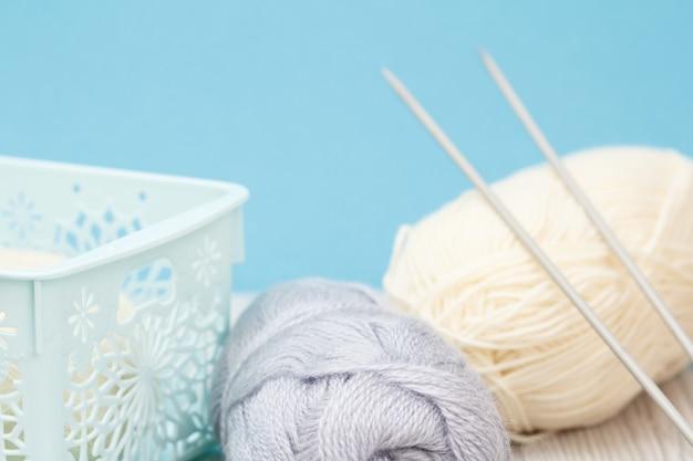 Nahaufnahme von strickgarnkugeln mit metallstricknadeln, plastikkorb in blauem hintergrund. strickkonzept. geringe schärfentiefe.