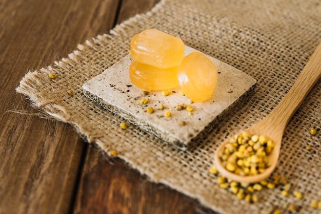 Nahaufnahme von süßen süßigkeiten und von bienenblütenstaubkernen auf sackstoff