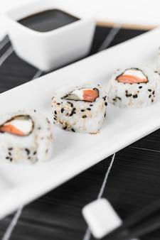 Nahaufnahme von Sushi mit Sojasoße in der Schüssel auf Platzmatte