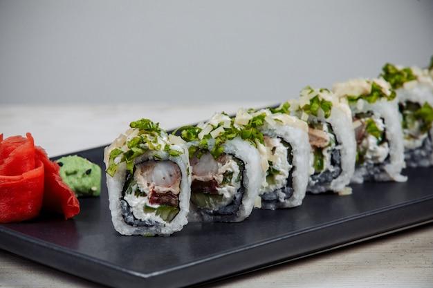 Nahaufnahme von sushi-rollen mit garnelen, frischkäse und gurke