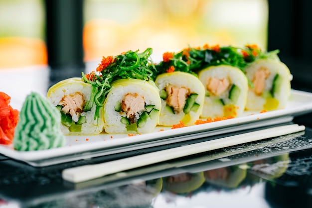 Nahaufnahme von sushi-rollen mit gebratenem lachs und gurke mit seetang und rotem tobiko gekrönt