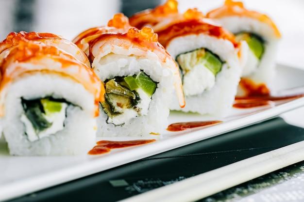 Nahaufnahme von sushi-rollen mit paprika-seetang und fisch mit garnelen bedeckt