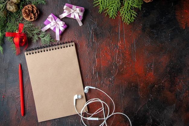 Nahaufnahme von tannenzweigen eine tasse schwarzen tee dekorationszubehör weißer kopfhörer und geschenk neben notebook mit stift auf dunklem hintergrund